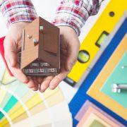 Kinderhand hält Miniaturhaus