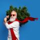 Weihnachtsmann mit Sonnenbrille und Tanne auf der Schulter