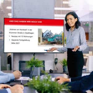 Frau neben Bildschirm mit Unternehmenspräsentation
