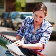 Frau entfernt Zettel von Winschutzscheibe eines Autos