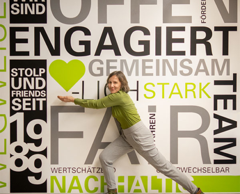 Andrea Stolp präsentiert die neue Wandgestaltung im stolp+friends-Büro