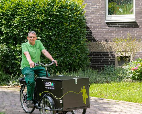 GEWOBAU-Hausmeister fährt mit gestaltetem Lastenrad