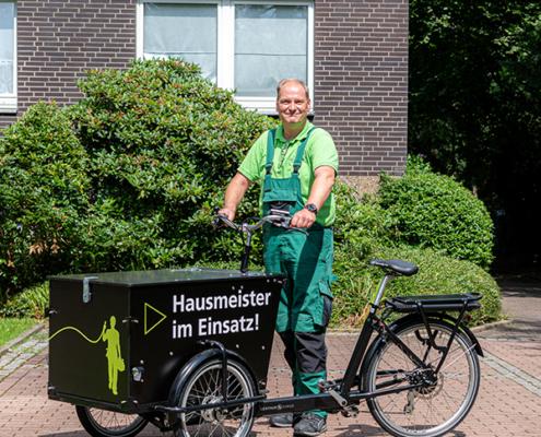 GEWOBAU-Hausmeister steht neben gestaltetem Lastenrad